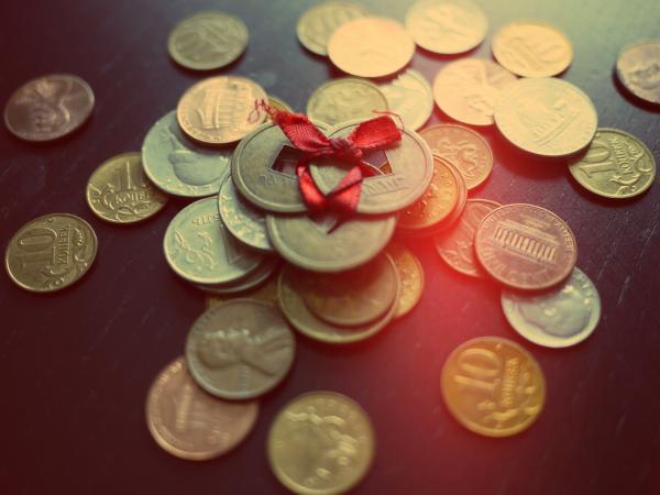 nhiều loại tiền và ruy băng đỏ xung quanh đồng tiền Trung Quốc