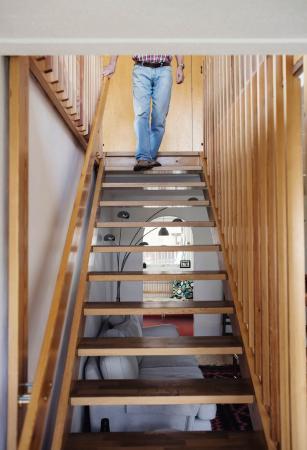 Người đàn ông bước xuống bậc thang gỗ