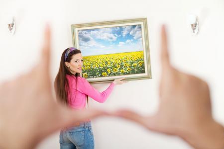 Người phụ nữ treo tranh nghệ thuật trên tường