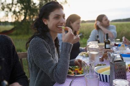Người phụ nữ mỉm cười ăn uống với bạn bè